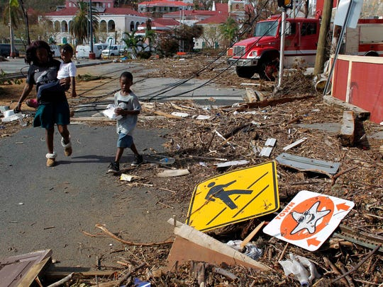 A woman with her two children walk past debris left