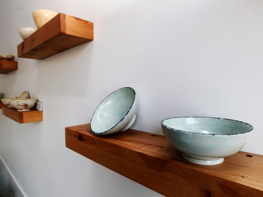 Bowls by artist Cathy Elsinger of Studio Cielo dress up a wall at Bowls restaurant. The bowls are for sale.