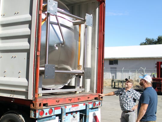 John Hutchings, right, looks on as work crews prepare to unload a tank at the new location for Fall River Brewing Co. in south Redding.