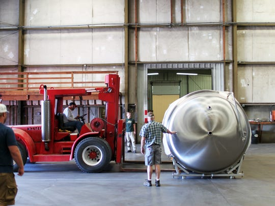 File photo - John Hutchings, far right, president and co-owner of Fall River Brewing Co., looks on in September 2017 as crews unload a tank at the brewery's location on Eastside Road in south Redding.