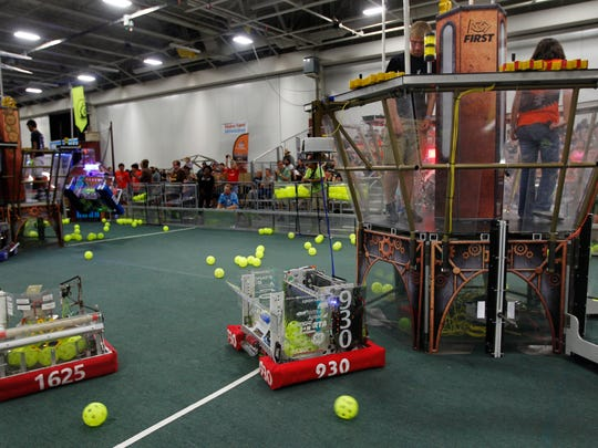 Robots are powered to pick up balls and gears during a competition at the Maker Faire on Saturday at State Fair in West Allis.