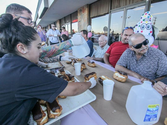 "Employee Carman Rangel (19) ""LEFT"" serves eclairs to contestants prior to Cannon's Bakery inaugural eclair eating contest Thursday, Sept. 28, 2017, at Cannon's Bakery in Newark, DE."