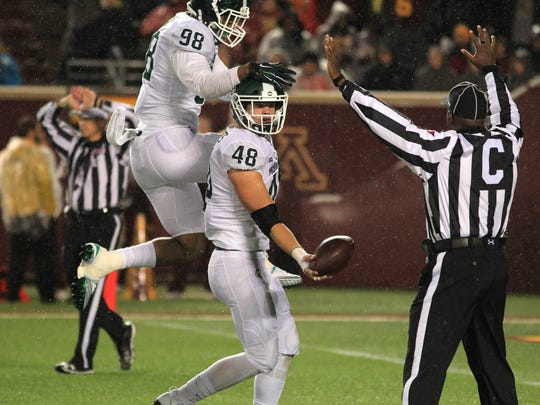 Michigan State sophomore defensive end Kenny Willekes, right, tosses the ball to an official after recovering a fumble at Minnesota as teammate Demetrius Cooper celebrates on his back. Willekes and Cooper have had terrific seasons rushing the passer.