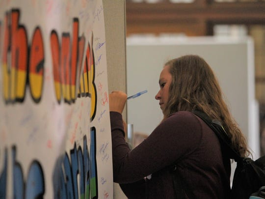 A Purdue student signs a banner that Amelia Earhart Elementary School students created to encourage diversity. The Earhart students were on campus Tuesday morning as part of a day or kindness.