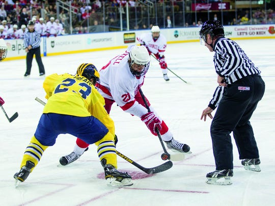 Shortly after winning this faceoff against Michigan's A. J. Treais, tri-captain Erik Axell made it 4–0 in favor of the Big Red in the third period.