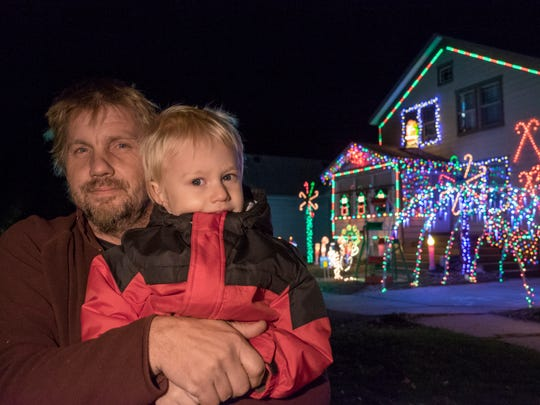 Derek Harper and his son, Jon Alan, 3, in front of his home, which is decorated in thousands of Christmas Lights, Nov. 16. Each year, Harper decorates his house at 520 Main St. in Marine City with thousands of Christmas lights.