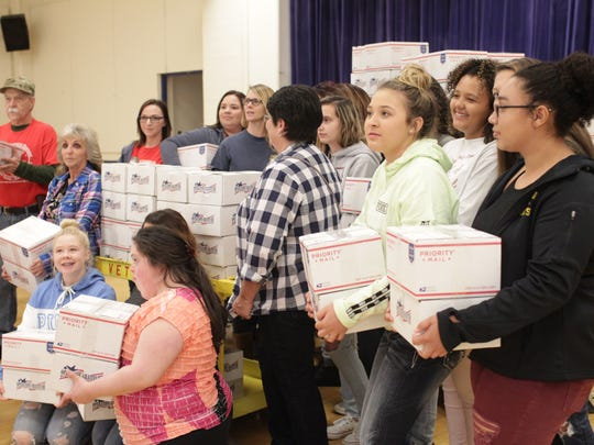 Volunteers pose with the boxes they prepared to send to veterans deployed abroad.