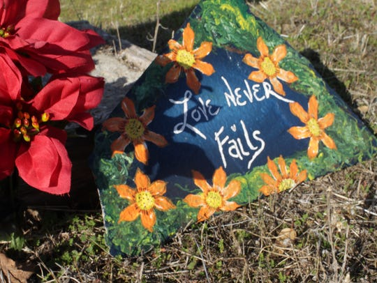 """A painted rock reads """"Love Never Fails"""" at the entrance"""