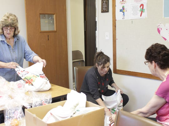 Beverly Gano, Lisa Kassik and Carole Sievers pack bags of food for Christmas at the Rancho Tehama Community Church.