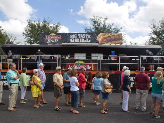 People wait in line for free brats as grill masters