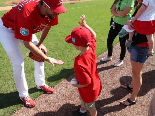 Adam Wainwright, who made his debut with the Cardinals back in 2005, struggled with injuries last season, but will enter the New Year healthy and looking to get back on track. Pictured, he connects with a young fan.