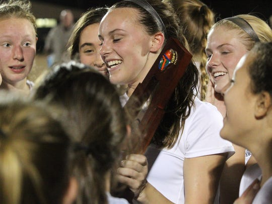 Leon's Madison Rumenik holds the district championship trophy after the Lions beat Lincoln 2-0.