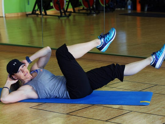 Catherine Andersen, owner and personal trainer of Adventure Boot Camp and Achieve Personal Fitness at Balance Fitness demonstrates the ending position for the bicycle crunch exercise.