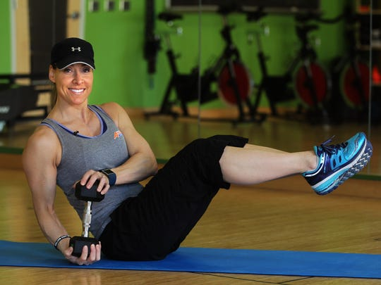 Catherine Andersen, owner and personal trainer of Adventure Boot Camp and Achieve Personal Fitness at Balance Fitness demonstrates the advanced position for the Russian Twist exercise using a weight.