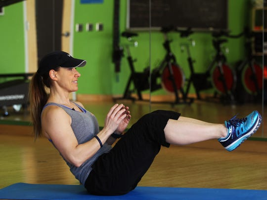 Catherine Andersen, owner and personal trainer of Adventure Boot Camp and Achieve Personal Fitness at Balance Fitness demonstrates the starting position for the Russian Twist exercise.