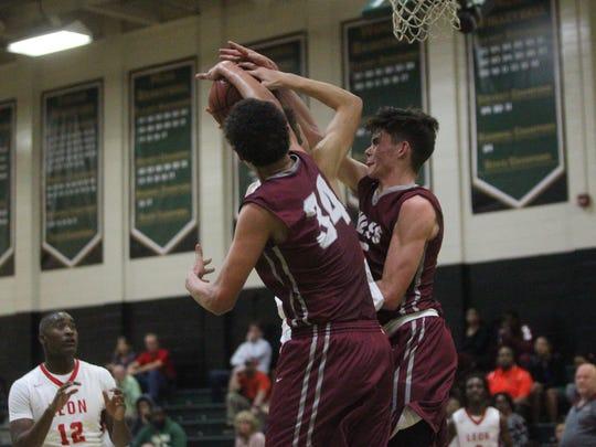 Leon's Northern Harvey and Caleb Smith block a shot