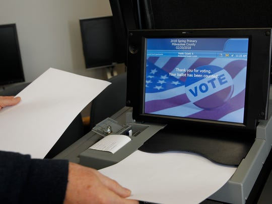 Test ballots are fed into an electronic tabulator by