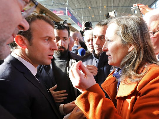 An unidentified woman protests at French President Emmanuel Macron and French Agriculture Minister Stéphane Travert, left, as they visit the 55th International Agriculture Fair at the Porte de Versailles exhibition center in Paris, France, Saturday, Feb. 24, 2018. The fair, featuring farm animals, food and agriculture industry, will last until March 4, 2018.