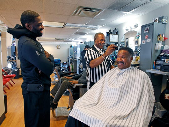 "Gaulien ""Gee"" Smith of Gee's Clippers (left) stops in to chat with long time barber Ceree Huley and his client Ronald Roberts."