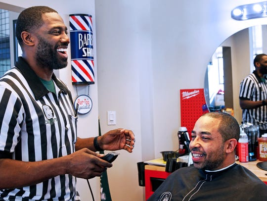 "Longtime barber and owner Gaulien ""Gee"" Smith of Gee's Clippers cuts the hair of Richard Armstead, a fellow barber."