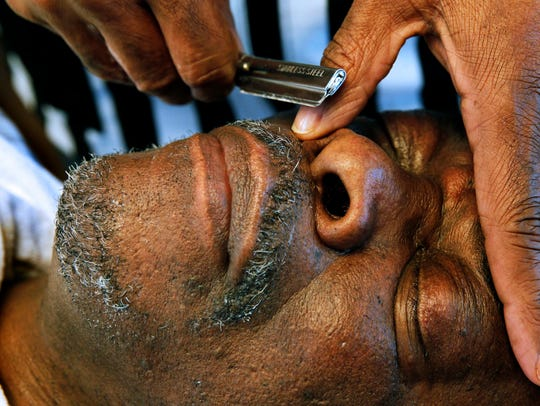 Ceree Huley, from Gee's Clippers, shaves his brother, Charles Huley.
