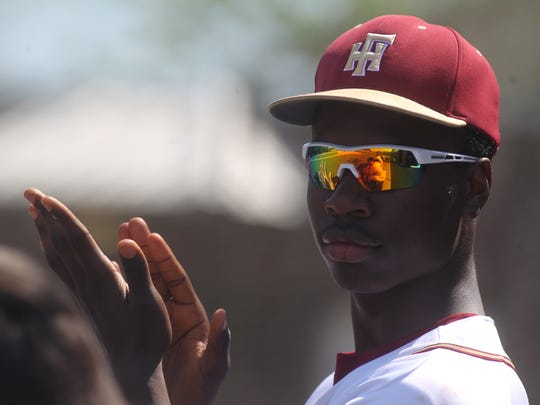 Florida High freshman Argene Lynn cheers on his team in the dugout.