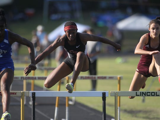 Florida High's Tonie Morgan clears a hurdle during