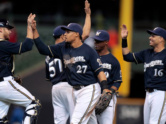 Milwaukee Brewers center fielder Carlos Gomez (27) celebrates with Milwaukee Brewers catcher Jonathan Lucroy (20) and other teammates after the Milwaukee Brewers 5-1 win over the St. Louis Cardinals   at Miller Park on April 16, 2014.