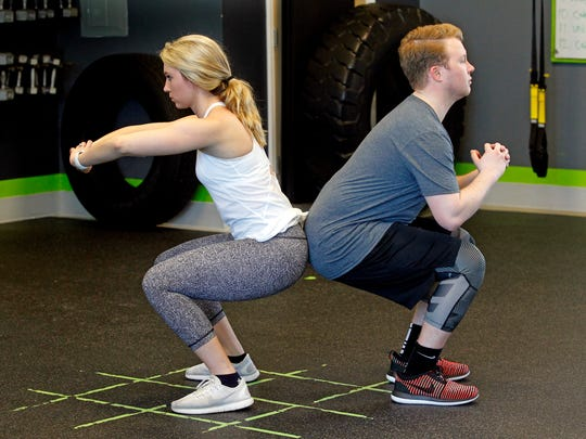 Courtney Tarmann and Nathan Kowalczyk demonstrate the  ending position for the partner wall sit exercises at bodyfuel inc.