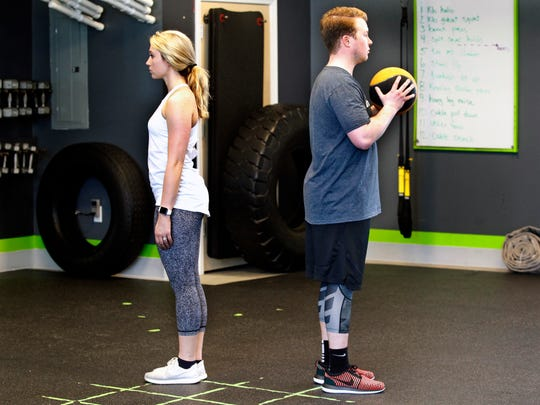 Courtney Tarmann and Nathan Kowalczyk demonstrate the starting position for the reverse lunge with medicine ball exercises at bodyfuel inc. Eric Gramza designed this program to help couples prepare for their weddings.