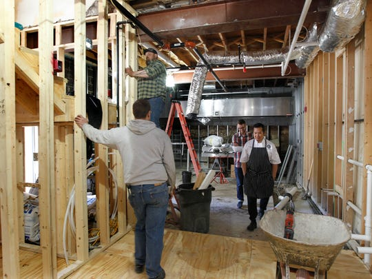 Executive chef Thi Cao (right) and Britt Buckley (behind Cao), pass through one of the new kitchen areas under construction in the expansion of Buckley's Restaurant & Bar. There will be two kitchens, two fireplaces and two bars when the expansion is complete.