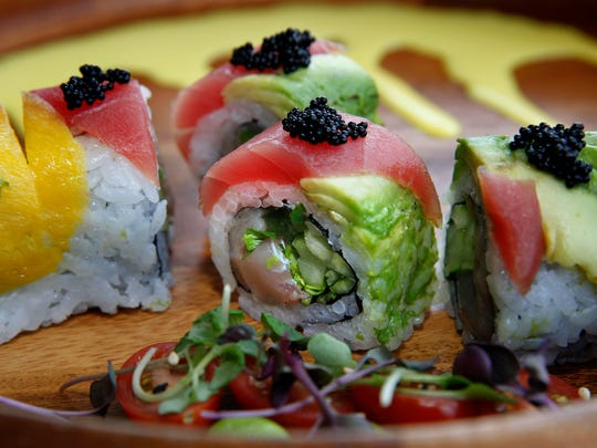 The La Fiesta roll at Hungry Sumo, shown here with salmon inside, is topped with tuna, mango, avocado and black tobiko.