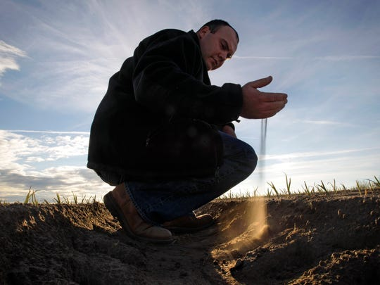 Farmer Aries Haygood shows how powdery the top layer of soil is on his freshly planted Vidalia onion farm in Lyons, Ga.,  on Dec. 10, 2010. The United States' extreme weather — flood-inducing downpours, extended droughts, heat waves and bitter cold and snow — has doubled in the 30 years since 1988, according to a federal index.