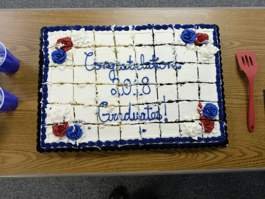 "Cake reads ""Congratulations 2018 Graduates!"" during"