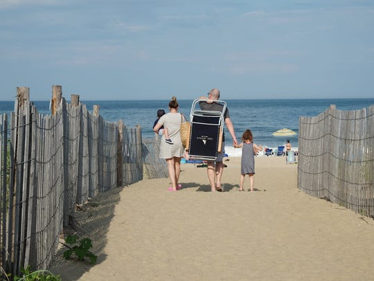 A family treks down toward the water in Rehoboth Beach