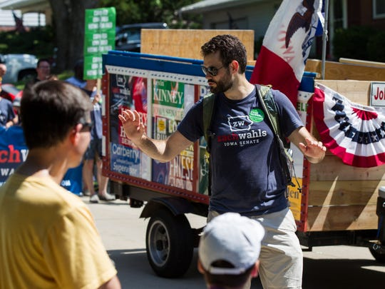 """Zach Wahls waves to supporters while walking with the Johnson County Democrats in the 4th Fest Parade in Coralville on Wednesday, July 4, 2018. The parade theme was a reference to Coralville's """"hub of hospitality"""" nickname it earned in the late 1960s."""
