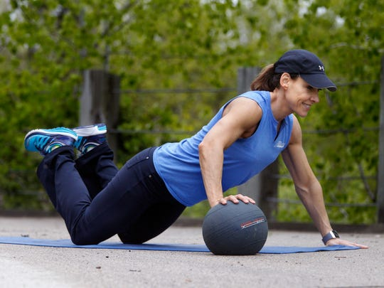 Catherine Andersen shows the starting position for the medicine ball pushup exercise.