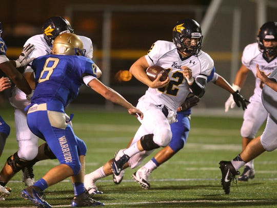 Victor QB Mike Wagner (12) finds a hole up the middle
