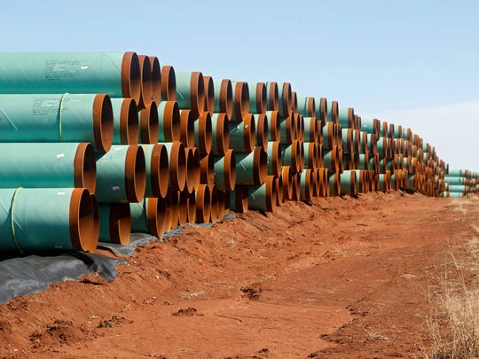In this Feb. 1, 2012, file photo, miles of pipe ready to become part of the Keystone Pipeline are stacked in a field near Ripley, Okla.