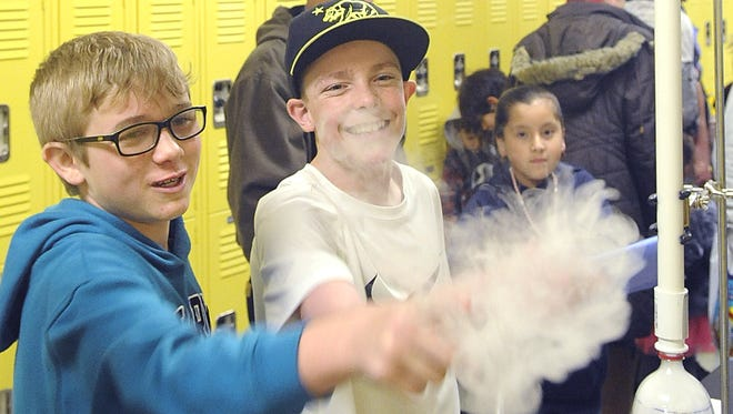 Silverland Middle School students Caleb Freeberg (left) and Kaden Aumann pop a bubble of dry ice and soap.