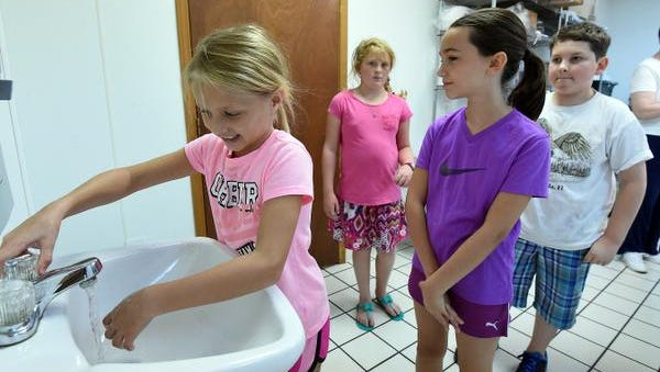 Bayli Teel, 8, washes her hands while Breanna Ford, 9, Aiden Tilly, 11, and Ally Williams, 9, wait their turn. The children learned the importance of cleanliness in the kitchen as part of a cooking class at L.C. Sammons Youth Center.