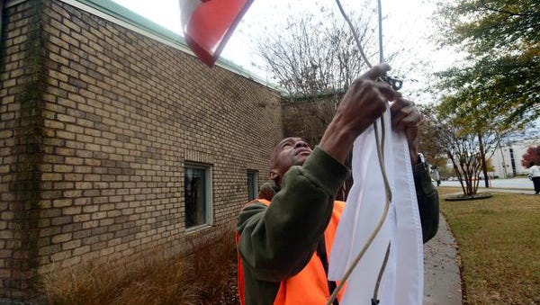Miracle Hill will again participate in the White Flag project, a system to let people know its overflow shelter is open.  Otis Sallie raises a white flag outside of the Miracle Hill Rescue Mission on Washington Street to let people know that the cold shelter will be open. (FILE PHOTO)