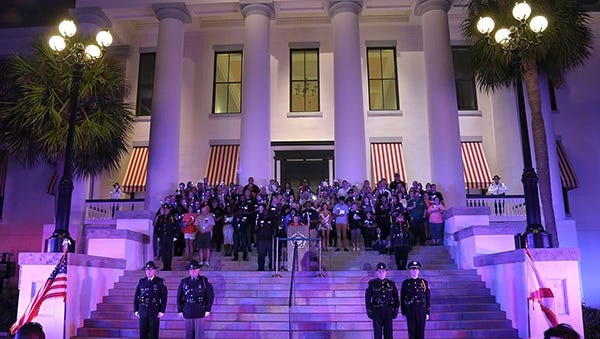 Family members of fallen law enforcement officers in Florida stand on the Capitol steps and hold blue lights in honor of their loved ones.