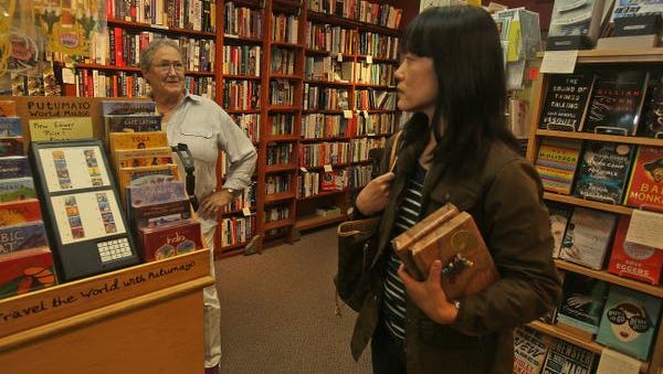 """Yvonne vanCourt, co-owner of Village Bookstore in Pleasantville, talks with customer Vivian Song of Katonah June 9, 2014. The two were chatting about Hillary Clinton's new memoir, """"Hard Choices"""" which hits store shelves on Tuesday. Song felt that it was smart for Clinton to release a memoir at this time if she is planning on running for President."""