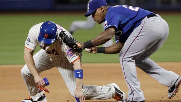 The Mets' David Wright is caught between second and third in a rundown by Texas Rangers third baseman Adrian Beltre in the fifth inning Saturday night at Citi Field.