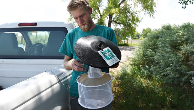 Will Schlatmann, surveillance supervisor with the Colorado Mosquito Control Northern Front Range Office, prepares a CO2 light trap  in Loveland on Monday, July 25, 2016.