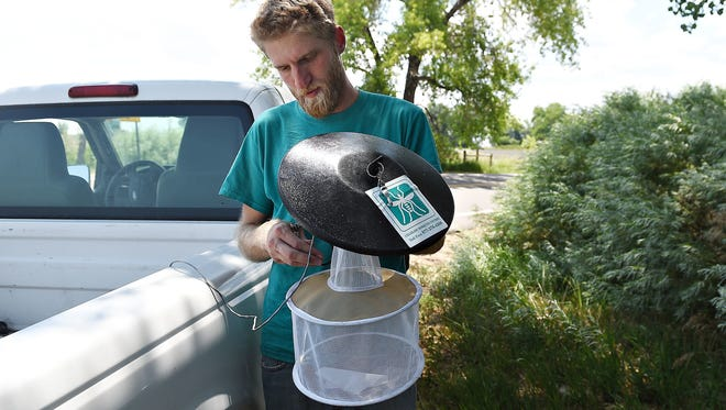 Will Schlatmann, surveillance supervisor with the Colorado Mosquito Control Northern Front Range Office, prepares a CO2 light trap in Loveland in this file photo.