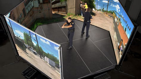 Two police officers train with a virtual simulator similar to the one the Fond du Lac Sheriff's Office will acquire.
