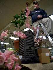 Jason Moles hangs flowers from the ceiling as he prepares