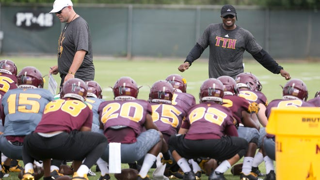 ASU's coaches look over the players as they stretch before a 2017 fall practice in Tempe.